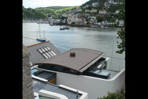 Seen from the road 20m up the cliff face, Riverhouse presents a shallow copper barrel-vault plus a jumble of other forms
